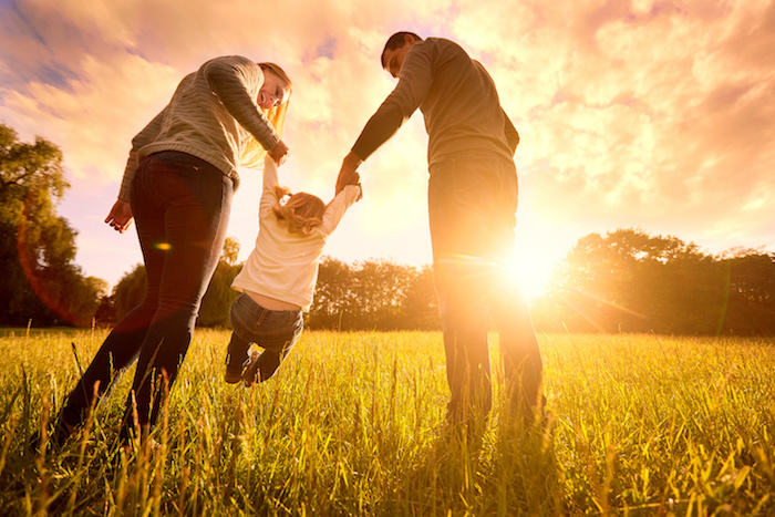 Parents hold the baby's hands.  Happy family in the park evening light. The lights of a sun. Mom, dad and baby happy walk at sunset. The concept of a happy family.