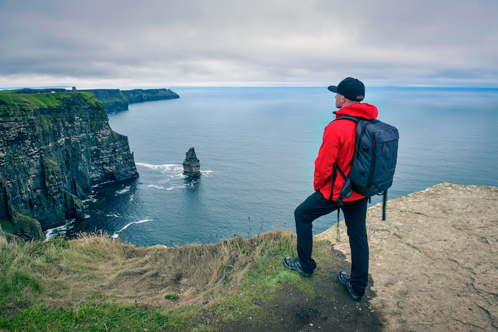 Young hiker standing at the cliffs of Moher